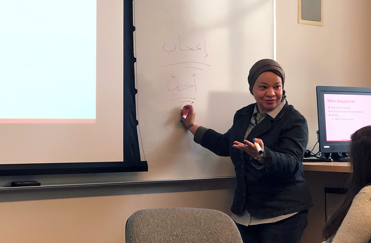 Hassan teaching her class as she writes on the whiteboard.