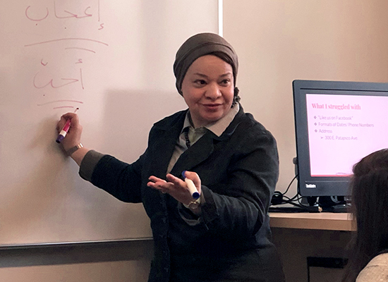 Inas Hassan, Ph.D. in front of a whiteboard, writing and teaching Arabic to her students.