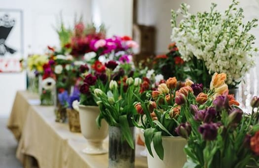 A large group of flowers in vases displayed on a table