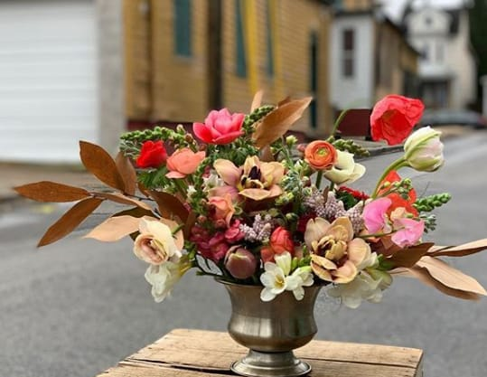 A vase full of flowers displayed outdoors