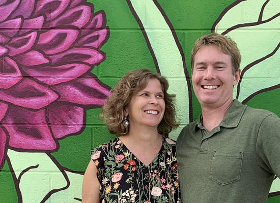Ellen Frost and Eric Moller posing in front of a wall mural of a flower
