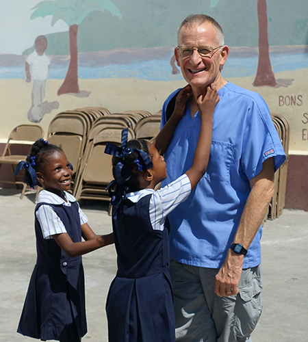 Haitian girls in school uniforms smile and laugh with the dentist.