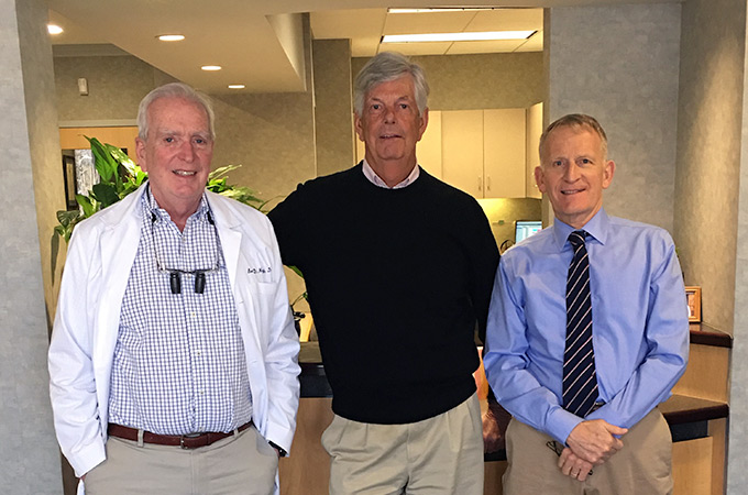 Doctors Barry, Jim, and Lew pose together by the office's front desk.