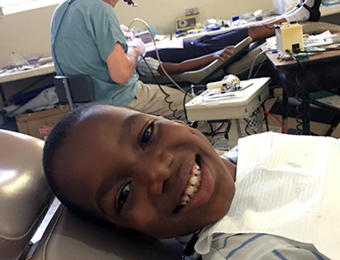 A Haitian child sits in a dentist chair smiling