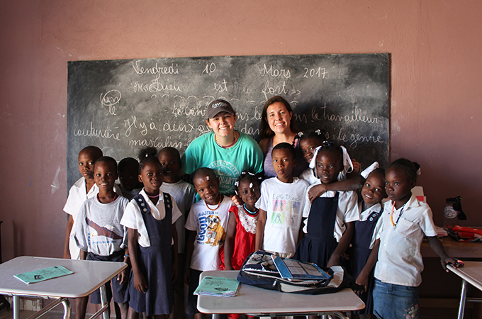 Julia and Ellie with Haitian students in classroom.