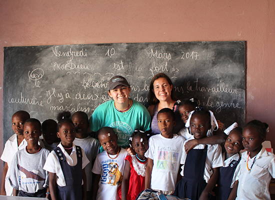 Two Loyola students stand with Haitian schoolchildren in front of a blackboard.