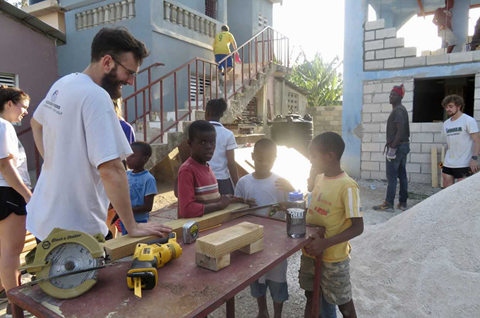 Loyola students working with Haitian school children outside.