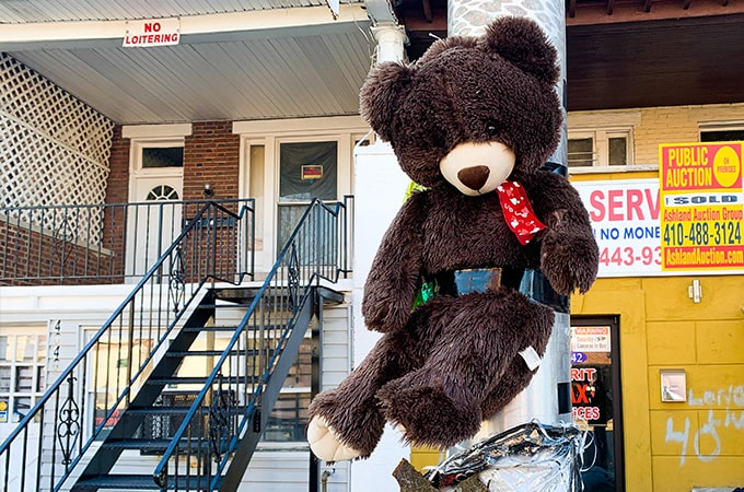 A teddy bear taped to a streetlight
