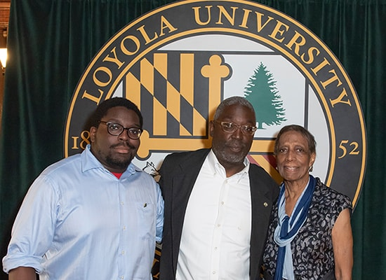 The Simms family (Tyler, Ed, and Louise) pose in front of the Loyola seal