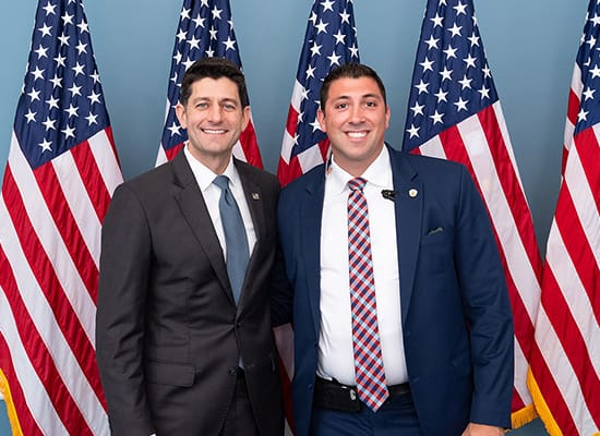Zach Samson and Paul Ryan standing in front of American flags