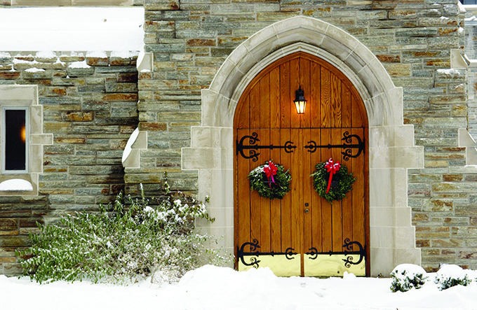 Front door of the Alumni Memorial Chapel in the snow decorated for Christmas