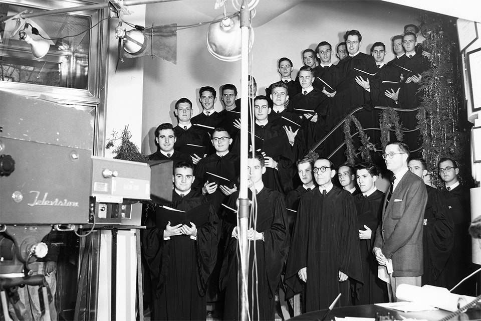 Loyola choir posing in front of a television camera for the 1953 Christmas concert