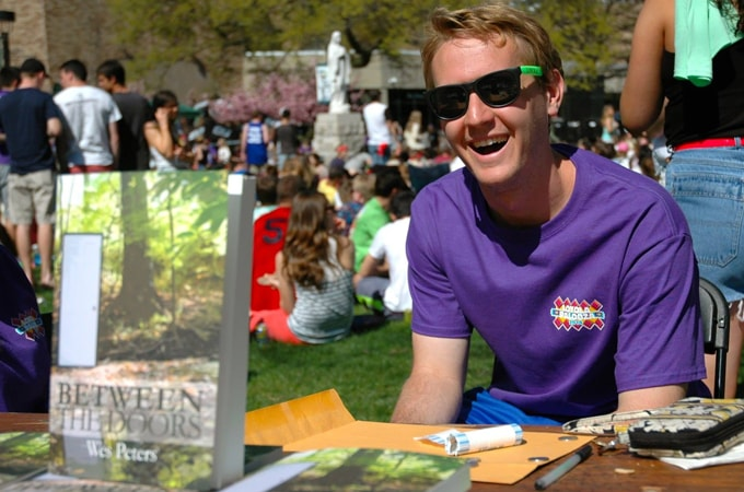 Student selling copies of Wes Peters's 'Between the Doors' on Loyola's Quad