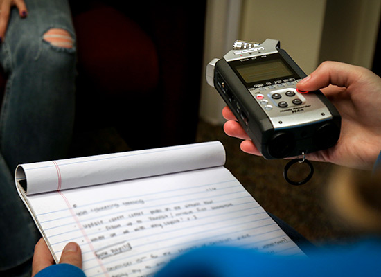 A student holding a voice recorder and notepad