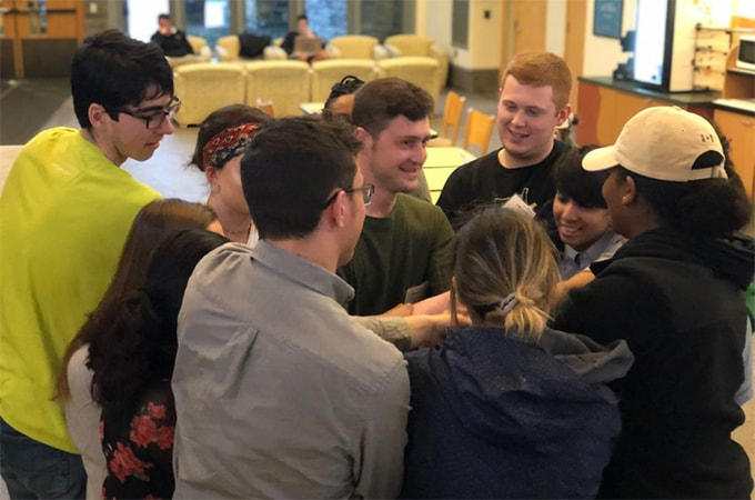 A group of students in the Social Impact Fellowship program huddle together to celebrate during a meeting