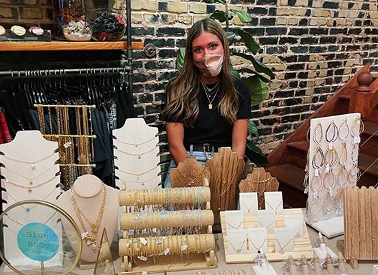 Maria Jaeckel sits at a table displaying her jewelry in a pop-up shop