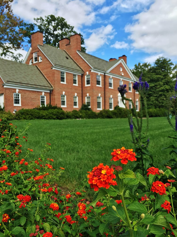 The red-bricked alumni house, with red flowers in the foreground
