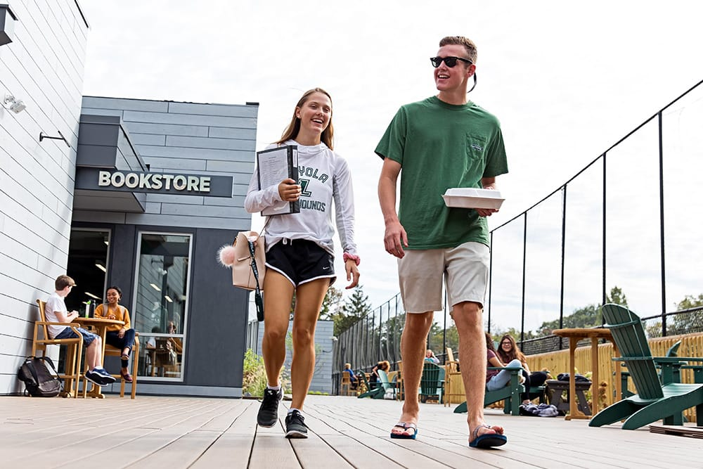 Two students walking on a wood deck, with the bookstore in the background, and other students sitting on chairs outdoors