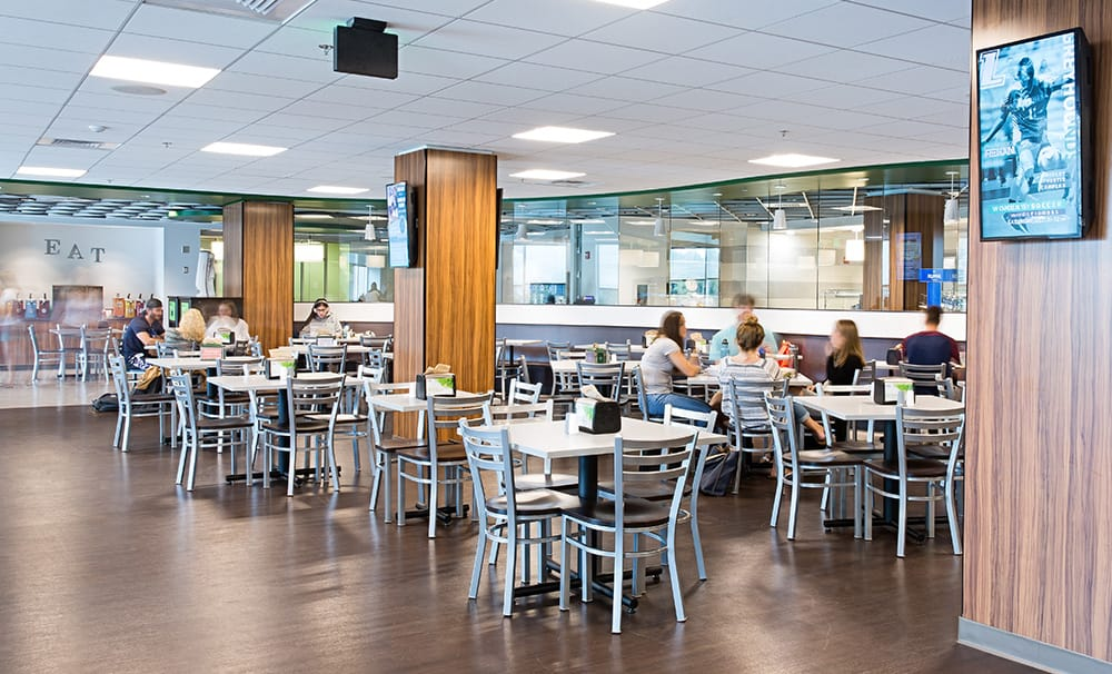 Dining facilities - wood columns, glass windows, faux-wood floor, and students sitting and chatting around tables
