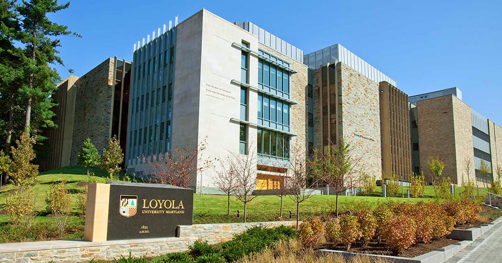 The tan-bricked facade of the Donnelly Science center as seen from the intersection of Cold Spring and Charles Street, with a Loyola sign in front