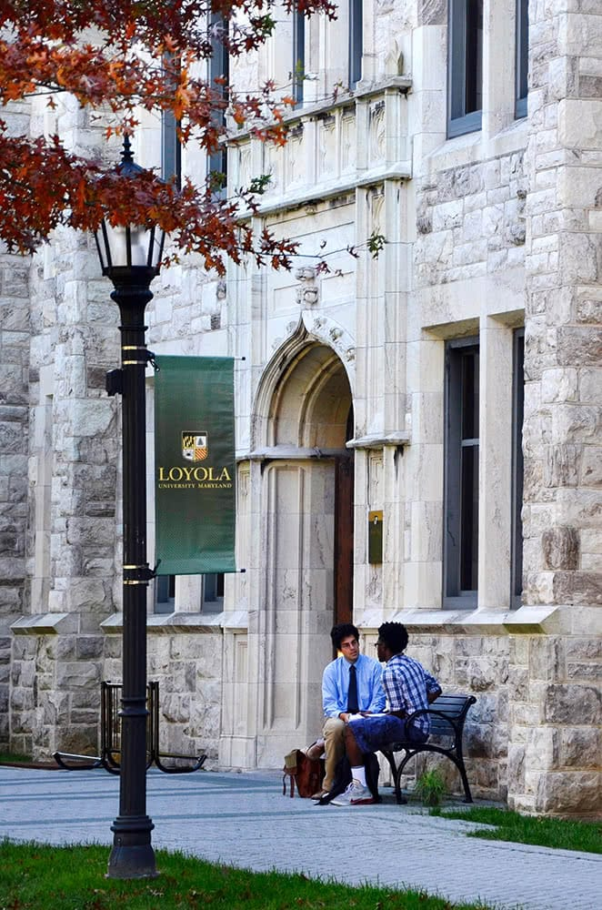 A student and professor sit on a bench in front of Beatty Hall