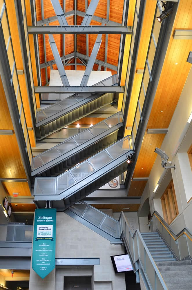 The towering interior of the Sellinger Building, with golden wood and metal staircases