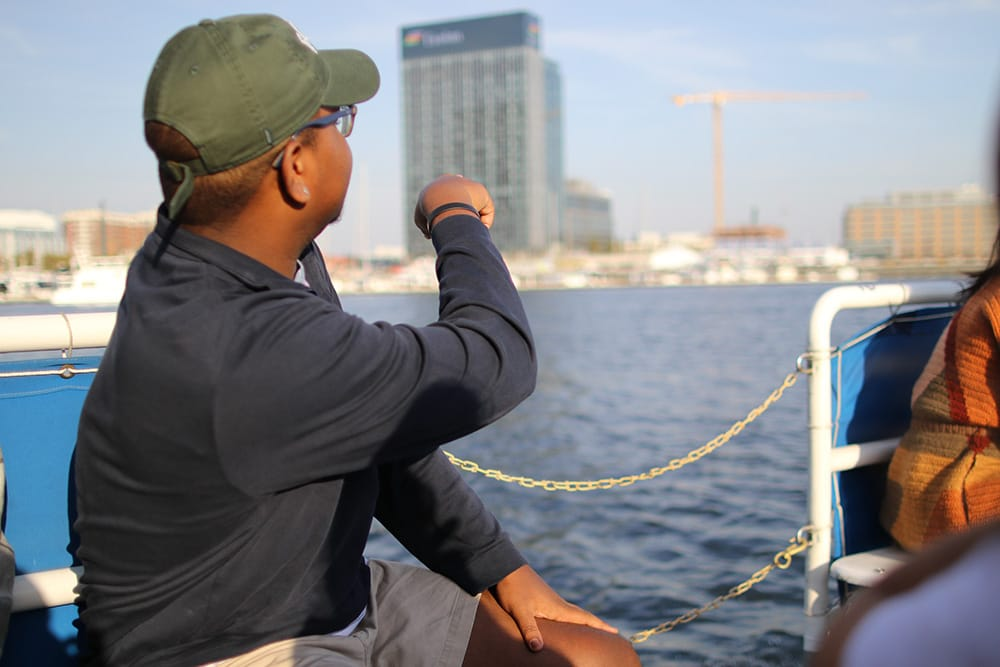 A student sitting on a boat in the bay and pointing toward a building on land