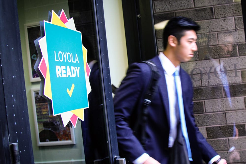 A student wearing a business suit walks out the door of a building with a sign that says 'Loyola Ready'