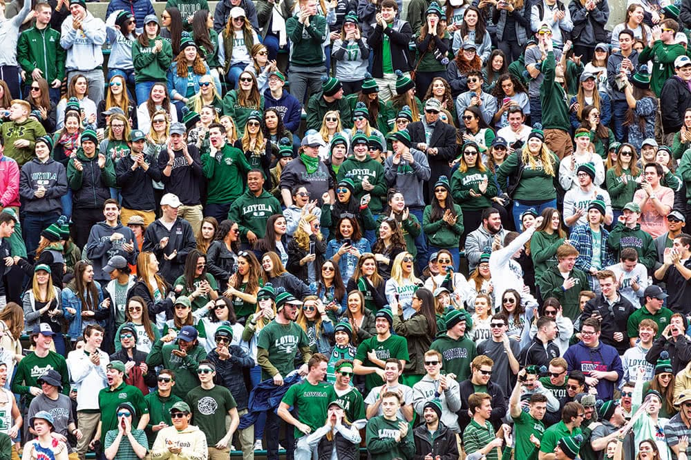 A large crowd at an athletics game - many wearing green, white, and grey shirts