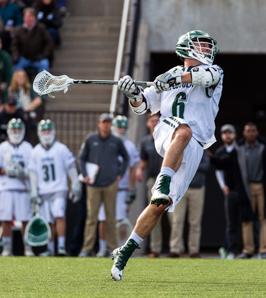 A men's lacrosse player swinging his stick about to throw the ball. Teammates can be seen in the background