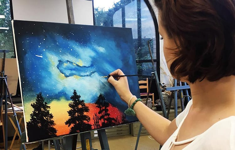 A student painting an outdoor scene with treetops and a glowing night sky