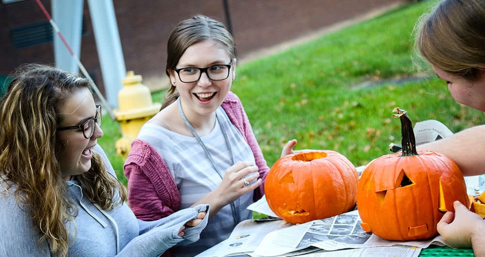Three female students carving small orange pumpkins outside