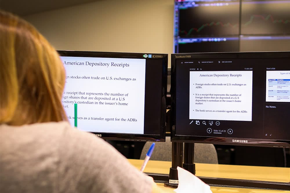 A view from behind of a student sitting in front of a computer screen, which displays information about American depository receipts