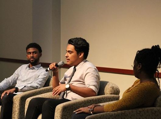Students on panel with microphone
