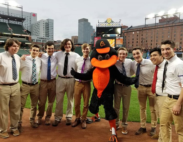 The Loyola Chimes and the Orioles mascot at an Orioles game on the field.