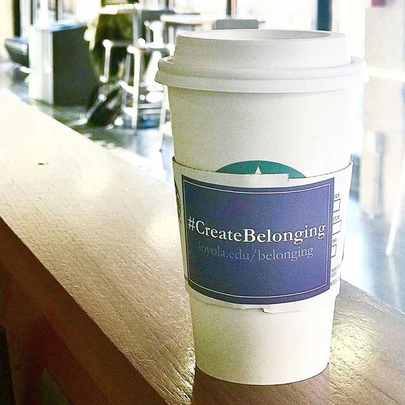 Starbucks cup with coffee sleeve reading #CreateBelonging