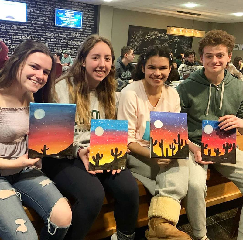Students proudly displaying their desert sunset paintings