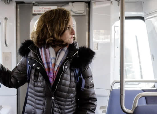 Margaret Wroblewski stands in an empty metro car looking to the side