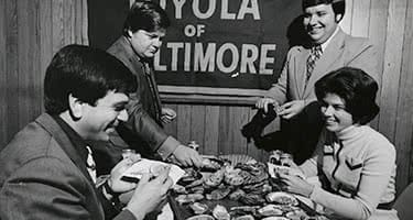 An old black and white photo of students eating oysters and crabs around a table
