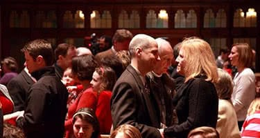 Couples standing closely and holding hands in the Alumni Memorial Chapel