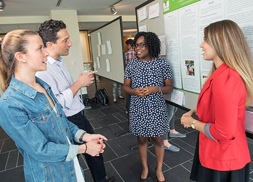 Students talking to a professor in front of a research poster