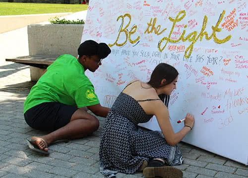 Students sitting on the ground writing a message on a board that says Be the Light
