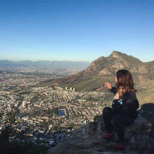 A student sitting on a mountain top, overlooking a city below