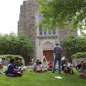 A class outside, sitting on the grass