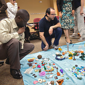Students in a Pastoral Counseling class looking at various objects spread out on the floor
