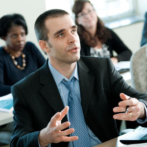 A business school student making a comment in class in the Loyola MBA, one of the top masters programs in Maryland.