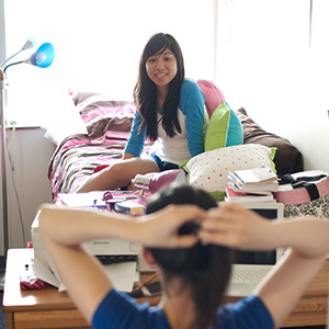 A girl sitting on her bed and smiling in her dorm room