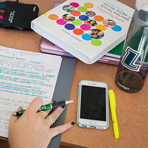A student's hand resting next to a notebook, phone, textbook, and Loyola water bottle