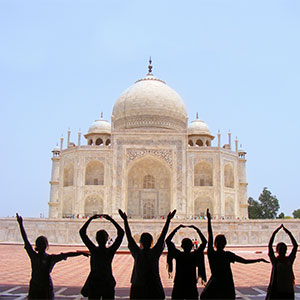 Students spelling out Loyola with their hands in front of the Taj Mahal