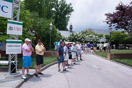 Golfers line up to watch the invitational
